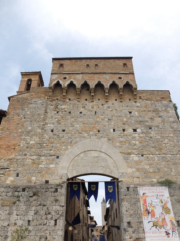 An arched entrance made of bricks is typical of the many entrances aroundComune di San Gimignano.
