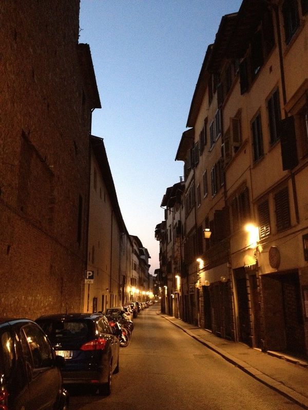 A lighted, still sleepy Florentine street at dawn without people and running vehicles. Only parked ones.